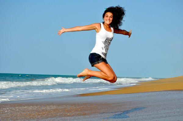 海辺でジャンプをする女性